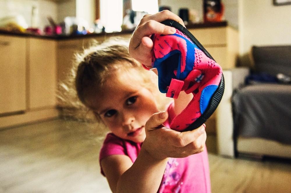 dziewczynka pokazuje jak bardzo elastyczne są buty dla dzieci typu barefoot